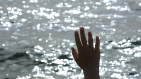 The hand of a little girl on sea background.  stock footage