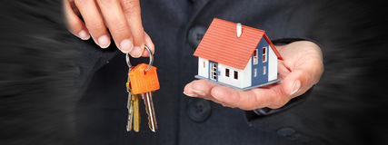 Hand with a little house and keys. Royalty Free Stock Photos