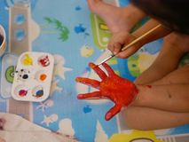 Hand of a little baby being painted with red and orange colors - baby handprint / fingerprint painting. Hand of a little young baby being painted with red and royalty free stock image