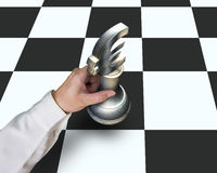 Hand locating Euro symbol piece on chessboard Stock Images