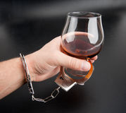 A hand locked to glass of alcohol Royalty Free Stock Images