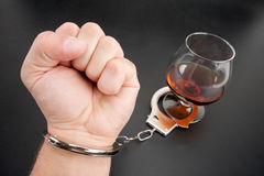 A hand locked to glass of alcohol Stock Images