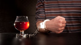 Hand locked to glass of alcohol Royalty Free Stock Photo