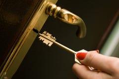 Hand, locking a key an iron door Stock Images
