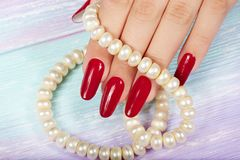 Hand with long artificial manicured nails colored with red nail polish. And a necklace Royalty Free Stock Photo