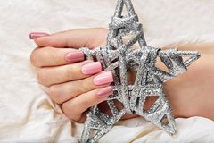 Hand with long artificial pink manicured nails holding a silver star Christmas toy. Hands with long artificial manicured nails colored with pink nail polish stock photography