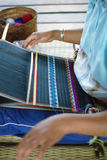 Hand loom. Shallow focus on a tribal woman in a northern Thailand village using a hand loom to make colorful cloth. Each tribe weave their own distinctive color Royalty Free Stock Image