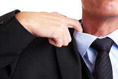 Hand loosen shirt. Business man loosens his shirt with his index finger Stock Image