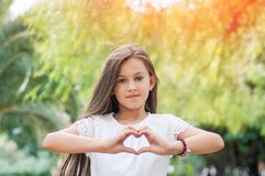 Hand love. Pretty little girl showing a heart symbol in the park royalty free stock photography