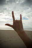 Hand with love symbol. On the beach royalty free stock image
