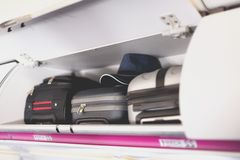 Hand-luggage compartment with suitcases in airplane. Carry-on luggage on top shelf of plane. Travel concept with copy. Space royalty free stock photos