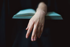 Hand lying on open book Stock Photo