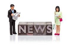NYHETERNA uttrycker i boktryck med läs- miniatyrfolk Arkivfoto