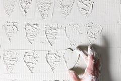 Hand machen Herzstempel auf weißer Gipswand Stockfotografie