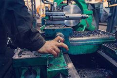 The hand of the machine operator creates a mechanical switch on the lathe.  royalty free stock photography