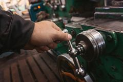 The hand of the machine operator creates a mechanical switch on the lathe.  stock photos