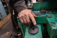 The hand of the machine operator creates a mechanical switch on the lathe.  stock photo