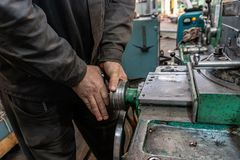 The hand of the machine operator creates a mechanical switch on the lathe.  royalty free stock photo