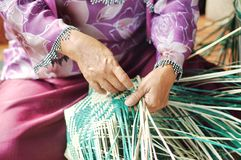 Hand made. The old woman weave a mat Stock Photo