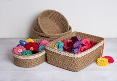 Crochet baskets with color knitted flowers on white background. Hand made baskets and color lace flowers Royalty Free Stock Images