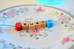 Hand made bracelet for children. Hand made bracelet sitting on a plate with a childs name on it, ruby Royalty Free Stock Image