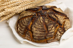 Hand made bread loaf with wheat ears on white wood Stock Image