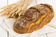 Hand made bread loaf with wheat ears on white wood Royalty Free Stock Photography