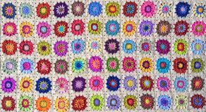 Patterned crochet blanket, background. A hand made brightly coloured, crocheted blanket, made up from numerous granny squares. Suitable as a background stock photos