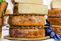 Hand made cheeses stacked. On wood exposed Royalty Free Stock Photos