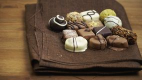 Hand made chocolate candies falling on wooden background, tasty sweets in slow motion stock video footage