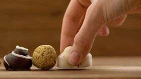 Hand made chocolate candies puting on wooden table womans hands studio stock video