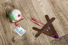 Hand crafted popsicle reindeer, and round ornament, laying on a wood grain background stock photo