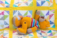 Free Hand Made Crochet Teddy Bear Lying On Quilt Cover Royalty Free Stock Photography - 121906427