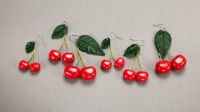Hand made custom cherry polymer clay earrings on grey fabric background stock photos