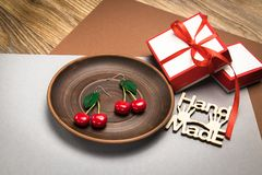 Hand made custom cherry polymer clay earrings on wooden plate royalty free stock photos