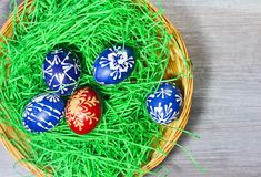 Hand made easter egg in green grass and basket on rustick wooden stock photo