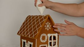 The hand-made eatable gingerbread house, adding by hand of icing on roof. And snow decoration stock video