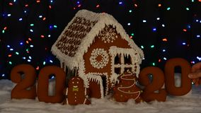 The hand-made eatable gingerbread house, adding by hand of zero in 2020 inscription, little man, New Year tree. Snow decoration, garland background stock footage