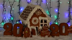 The hand-made eatable gingerbread house, adding by hand of zero in 2020 inscription, little man, New Year tree, snow decoration. Garland background stock footage