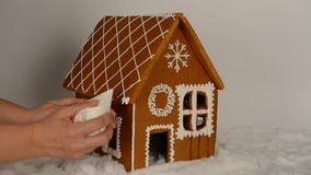 The hand-made eatable gingerbread house, adding by hand of icing on roof. And snow decoration stock footage