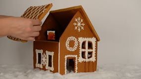 The hand-made eatable gingerbread house, adding by hand of part of roof. And snow decoration stock video footage