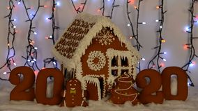The hand-made eatable gingerbread house, 2020 inscription, little man, New Year tree, snow decoration, garland. Background illumination stock video
