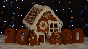 The hand-made eatable gingerbread house, 2020 inscription, little man, New Year tree, snow decoration, garland background. Illumination stock footage