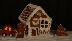 The hand-made eatable gingerbread house, little man, New Year tree, car, snow decoration, garland. Background illumination stock video footage