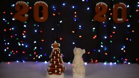 The hand-made eatable gingerbread house, mouse - symbol of year 2020, New Year tree, snow decoration. Garland background illumination stock video footage