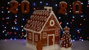The hand-made eatable gingerbread house, mouse - symbol of year 2020, New Year tree, 2020 inscription, snow decoration. Garland background illumination stock video footage