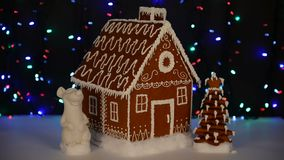 The hand-made eatable gingerbread house, mouse - symbol of year 2020, New Year tree, snow decoration. Garland background illumination stock footage