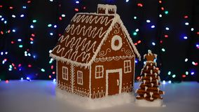 The hand-made eatable gingerbread house,  New Year tree, snow decoration. Garland background illumination stock footage