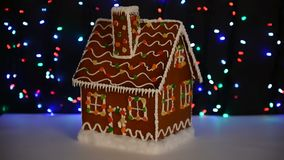 The hand-made eatable gingerbread house, snow decoration. Garland background illumination stock video footage