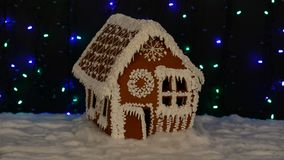 The hand-made eatable gingerbread house, snow decoration, garland background. Illumination stock video footage